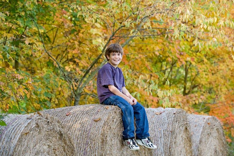 Junge, der auf Heu-Ballen sitzt stockfoto