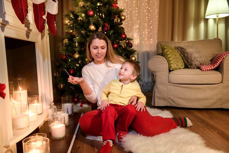 Junge, der auf ihren Mutterknien sitzt stockfoto