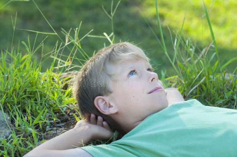 Junge, der auf Rasen des grünen Grases sich entspannt stockbilder