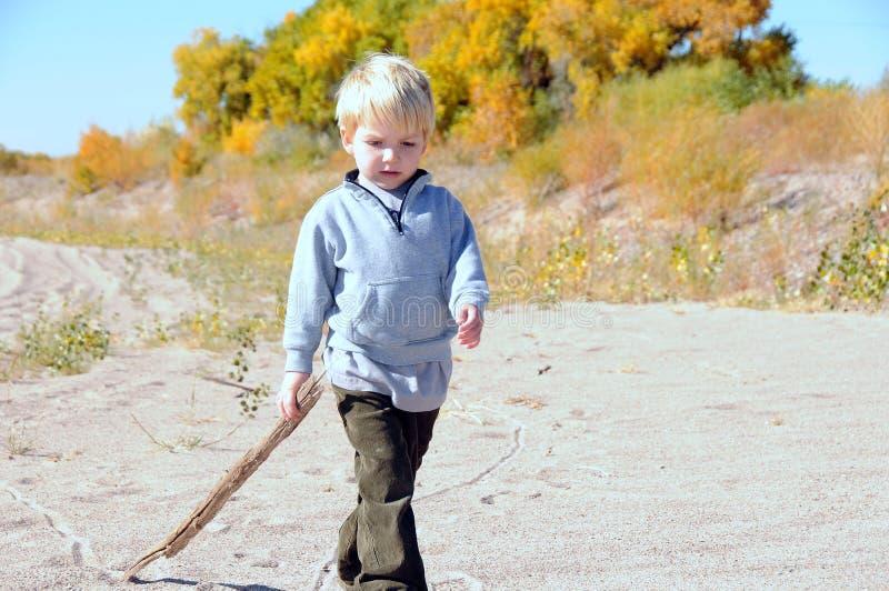 Junge, der auf Sand geht lizenzfreie stockbilder