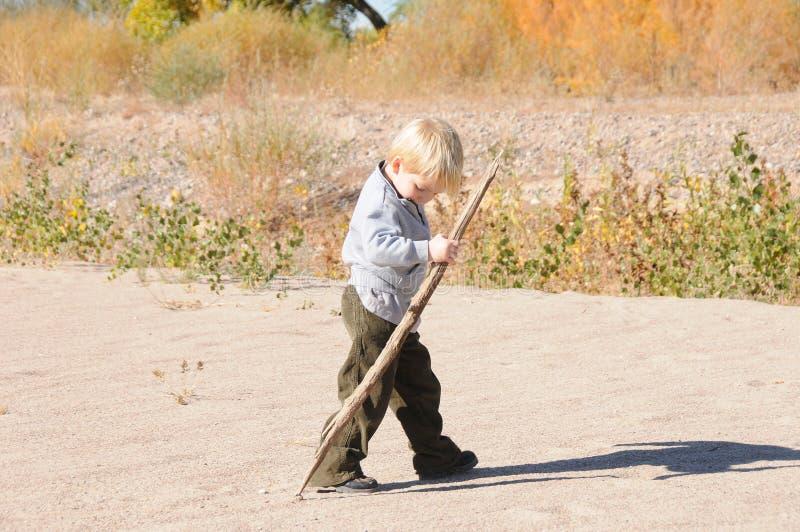 Junge, der auf Sand mit Steuerknüppel geht lizenzfreies stockbild
