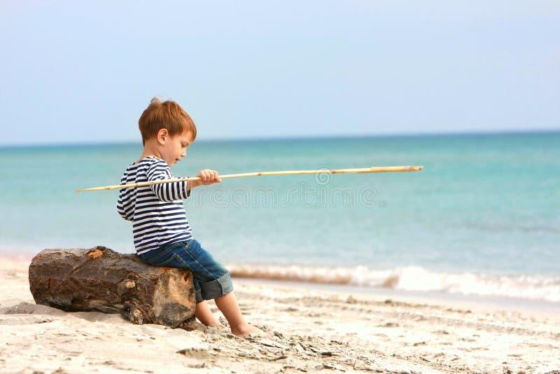 Junge, der auf Sandstrand sitzt lizenzfreie stockbilder