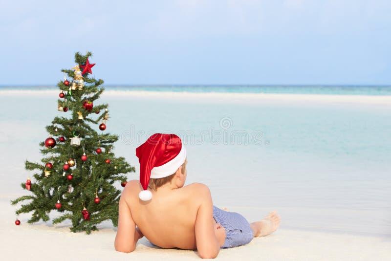 Junge, der auf Strand mit Weihnachtsbaum und Hut sitzt stockbilder