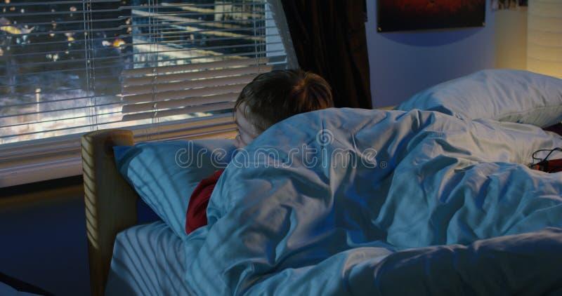Junge, der aus Fenster heraus beim Lügen im Bett schaut lizenzfreie stockbilder