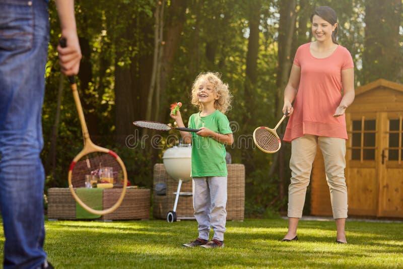 Junge, der Badminton mit Eltern spielt lizenzfreies stockbild
