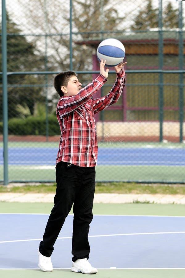 Junge, der Basketball spielt lizenzfreie stockbilder