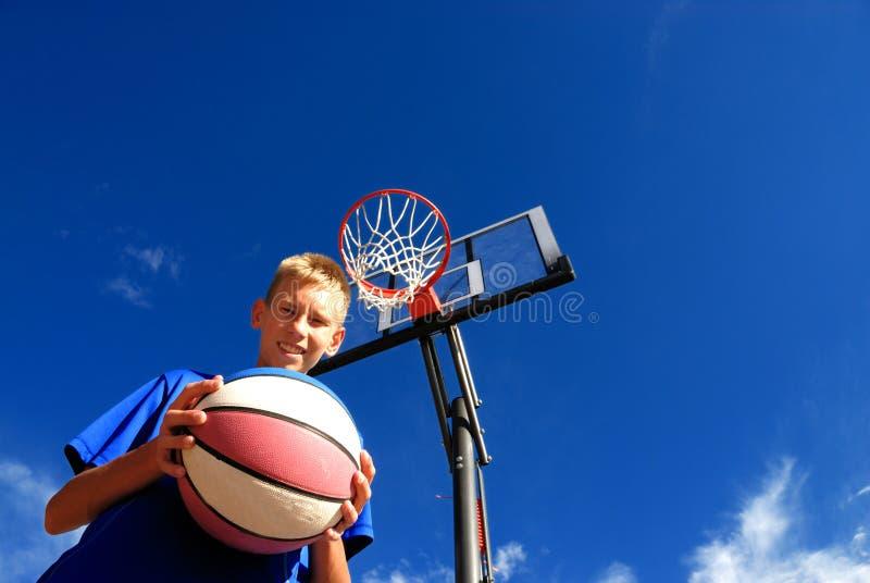 Junge, der Basketball spielt stockbild