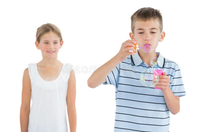 Junge, der Blasen während seine Schwester betrachtet ihn macht stockbild