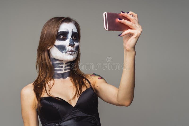 Junge der braunhaarigen Frau mit dem Erschrecken des Halloween-Skelettmakes-up unter Verwendung des rosa intelligenten Telefons a lizenzfreies stockbild