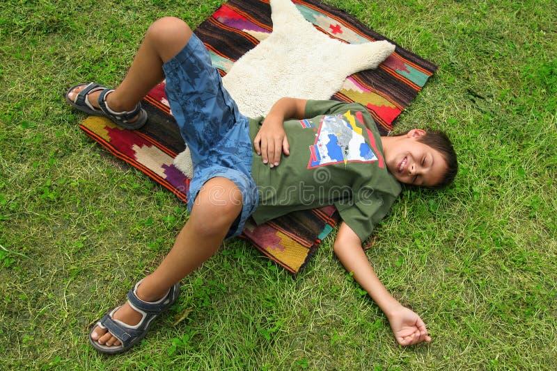 Junge, der in das Gras legt lizenzfreies stockfoto