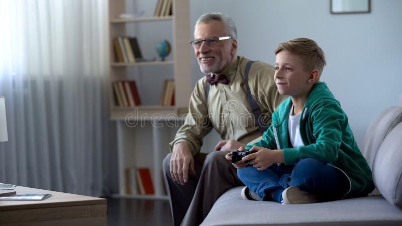 Junge, der das großväterliche Videospiel, zusammen spielend mit Konsole, glückliche Zeit zeigt stockbild