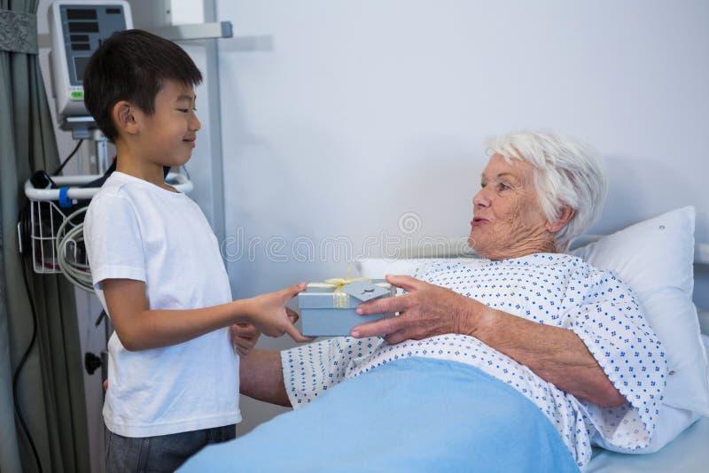 Junge, der dem älteren Patienten auf Bett ein Geschenk gibt stockfotos