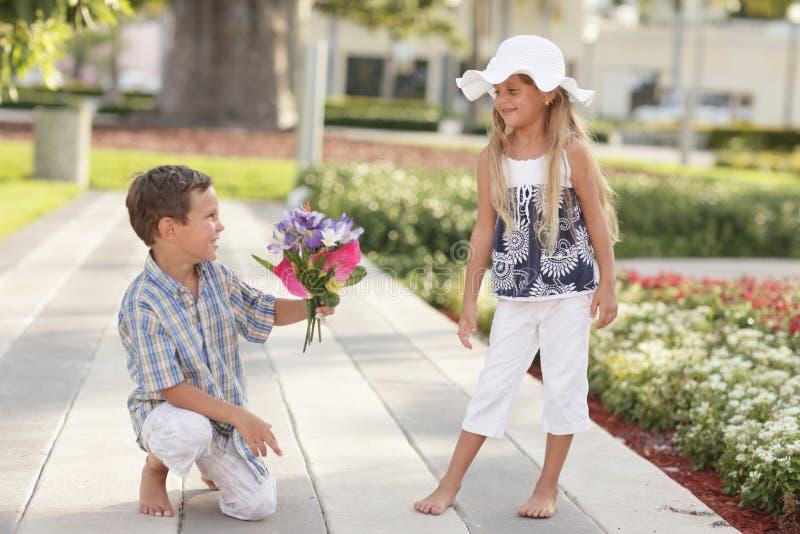 Junge, der dem Mädchen Blumen gibt lizenzfreies stockfoto