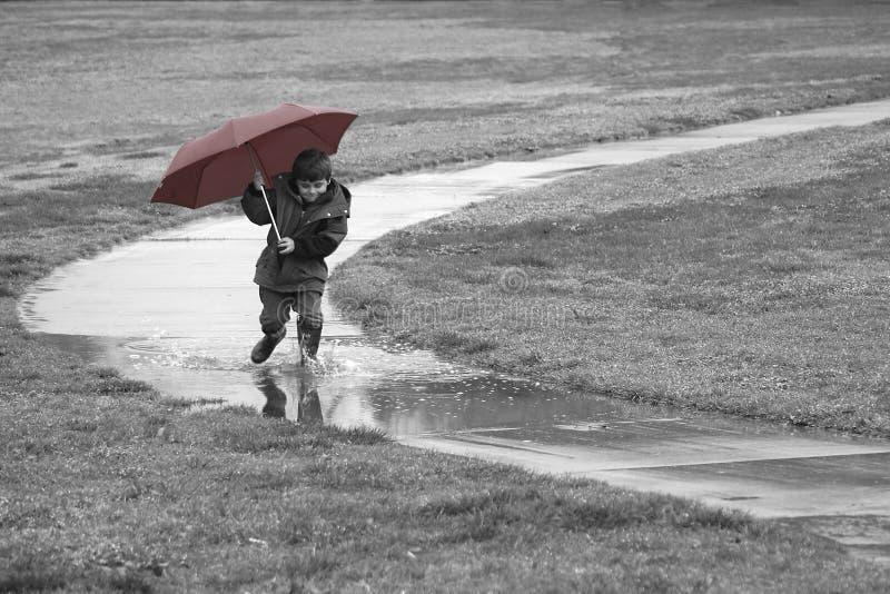 Junge, der in den Regen läuft stockbild