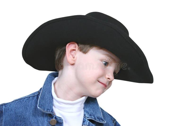 Junge in der Denim-Jacke und im schwarzen Cowboyhut stockfotografie