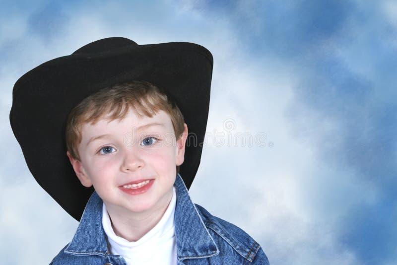 Junge in der Denim-Jacke und im schwarzen Cowboyhut lizenzfreie stockbilder