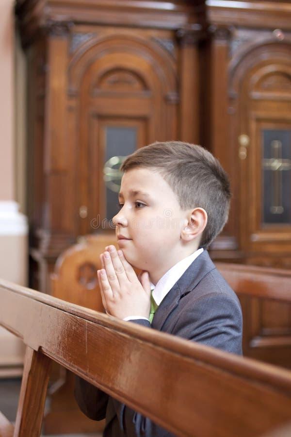 Junge, Der In Der Kirche Knit Und Betet. Stockbilder