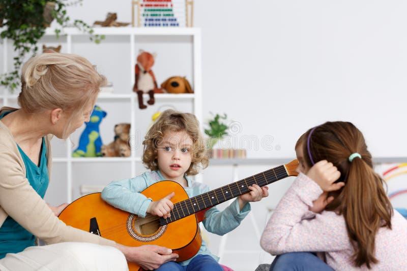 Junge, der die Gitarre spielt lizenzfreie stockfotos
