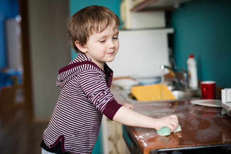 Junge, der die Küche säubert lizenzfreies stockbild