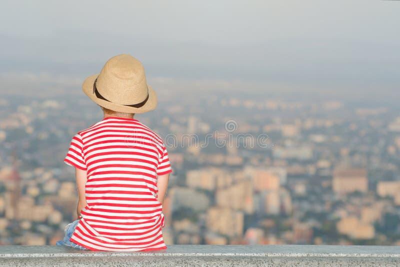 Junge, der die Stadt von einer Höhe sitzt und betrachtet Hintere Ansicht, Zeit glättend stockbilder