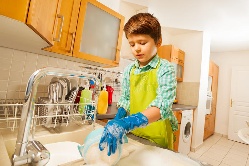 Junge, der die Teller unter fließendem Wasser in der Wanne tut lizenzfreie stockfotografie