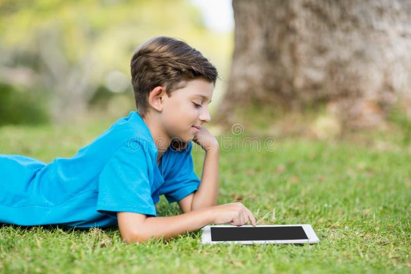 Junge, der Digital-Tablet im Park verwendet stockbild