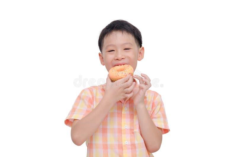 Junge, der Donut über Weiß isst stockfoto