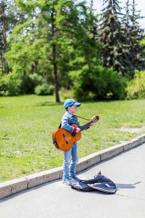 Junge, der draußen auf Akustikgitarre spielt Wenig Straßenmusiker KYIV UKRAINE am 1. Mai 2016 lizenzfreie stockfotos