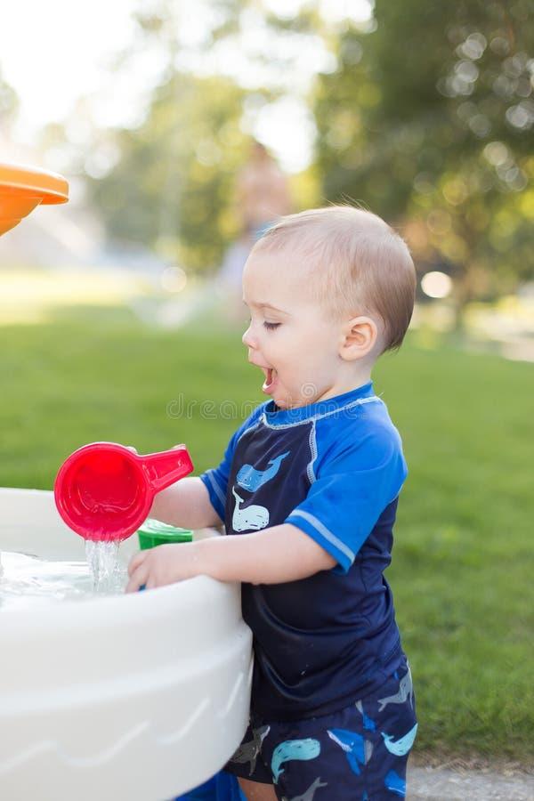 Junge, der draußen im Grundwasserspiegel spielt stockfoto