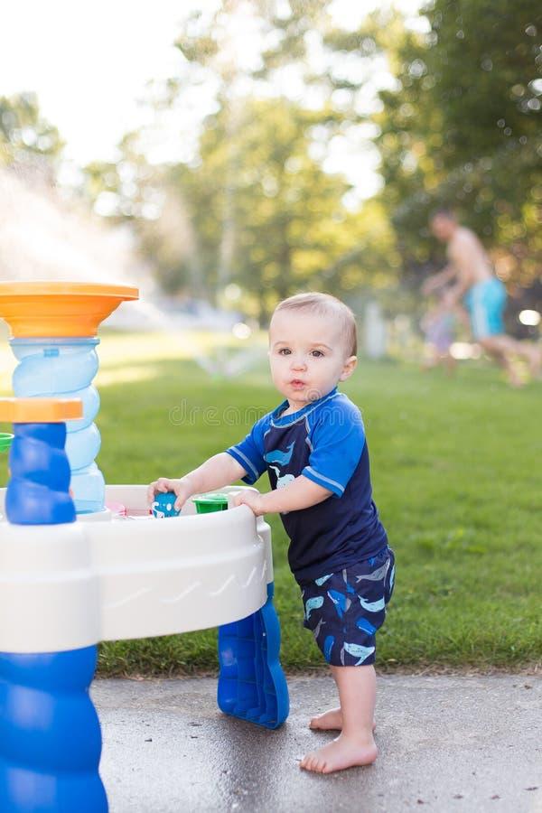 Junge, der draußen im Grundwasserspiegel spielt lizenzfreies stockbild