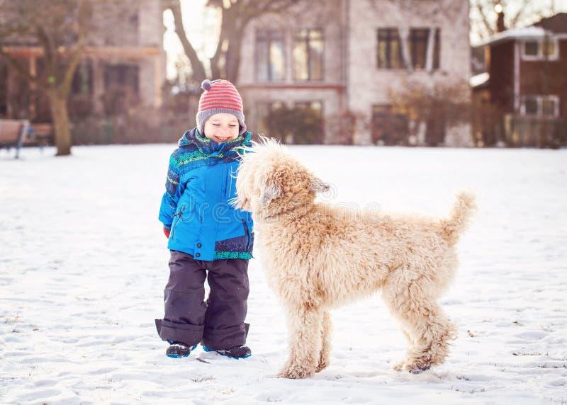 Junge, der draußen mit weißem Hund in Wintertag läuft und spielt stockfotos