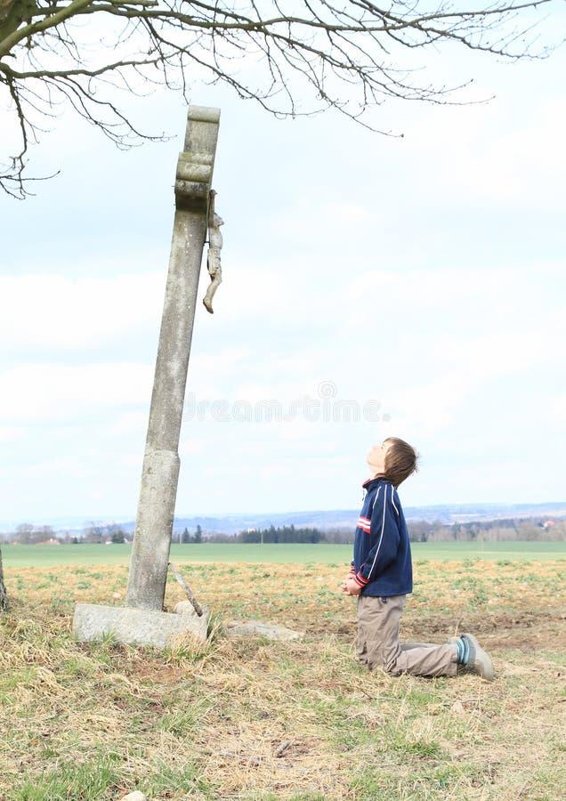 Junge, der durch Kreuz mit Jesus betet stockfotografie
