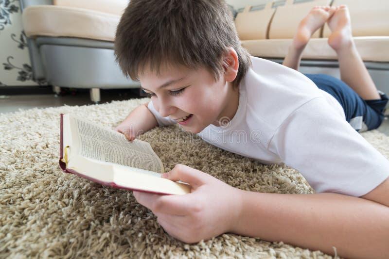 Junge, der ein Buch beim Lügen auf Teppich im Raum liest stockbild