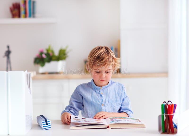 Junge, Junge, der ein Buch beim am Schreibtisch zu Hause sitzen liest lizenzfreies stockbild