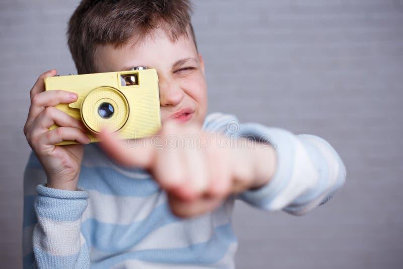 Junge, der ein Foto mit der Weinlesekamera zeigt auf Sie macht Photog stockfotografie