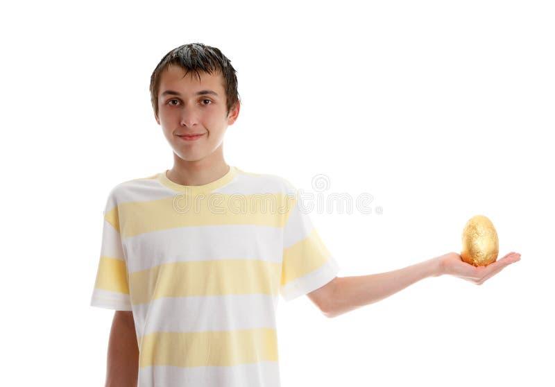 Junge, der ein goldenes Osterei anhält stockfotografie