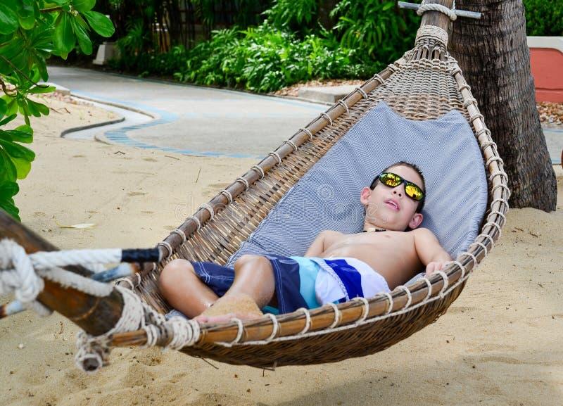 Junge, der ein hammoc auf schönem tropischem Strand genießt lizenzfreie stockfotografie