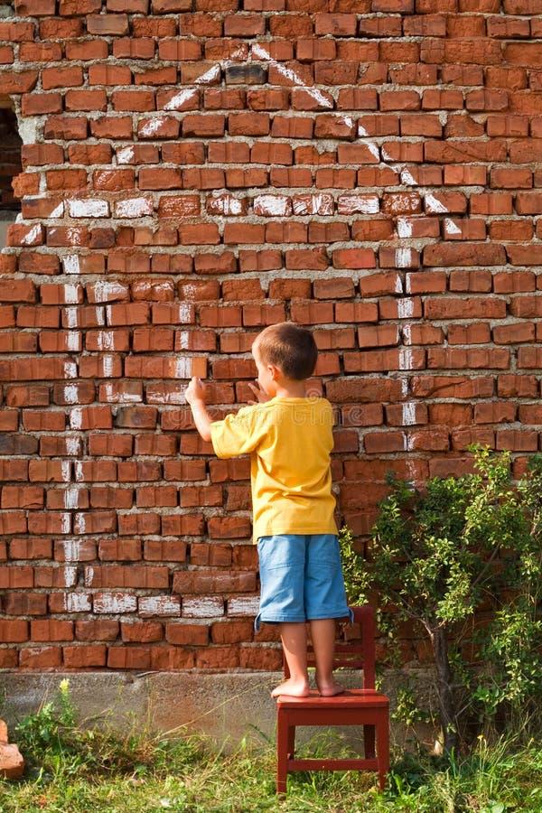 Junge, der ein Haus zeichnet lizenzfreies stockfoto