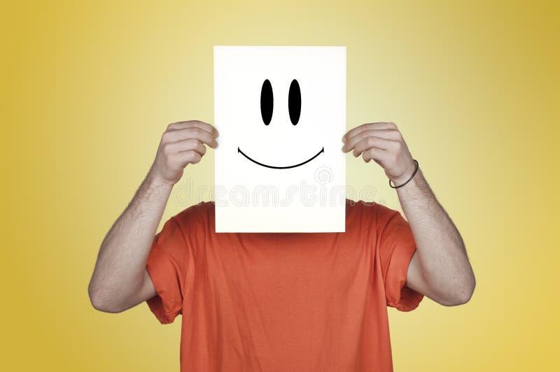 Junge, der ein leeres Papier mit einem glücklichen Emoticon zeigt stockbild