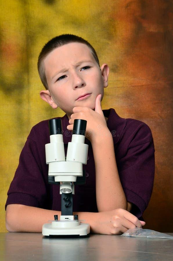 Junge, der ein Mikroskop verwendet lizenzfreie stockfotos