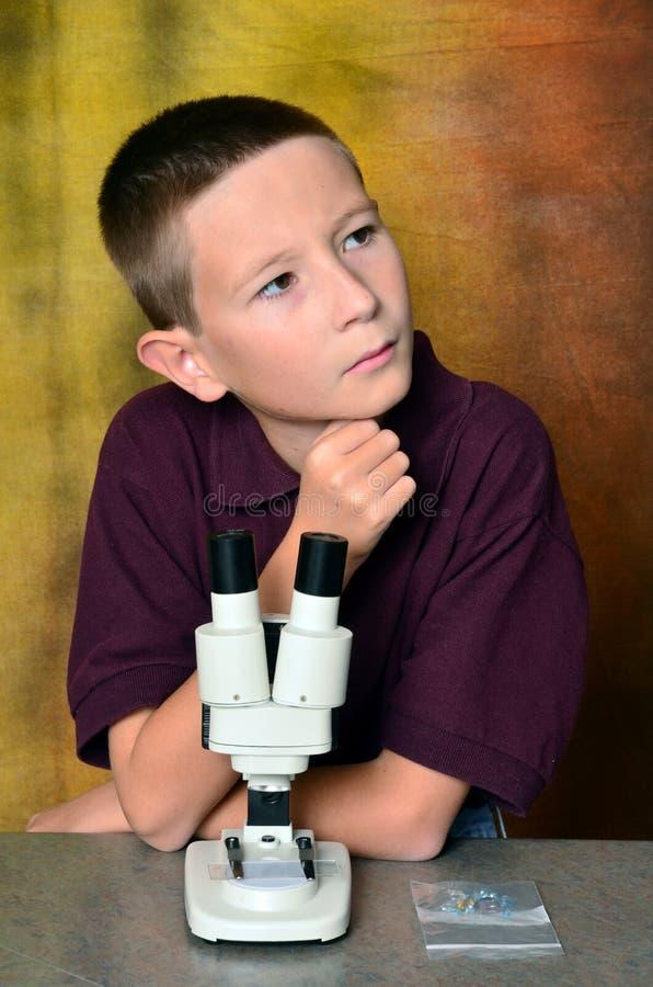 Junge, der ein Mikroskop verwendet lizenzfreie stockbilder
