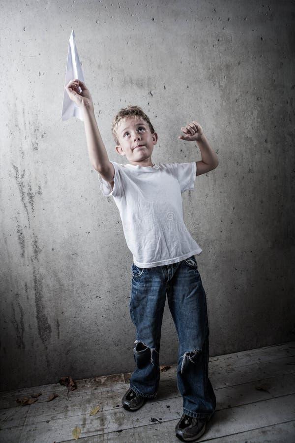 Junge, der ein Papierflugzeug fliegt stockfotografie