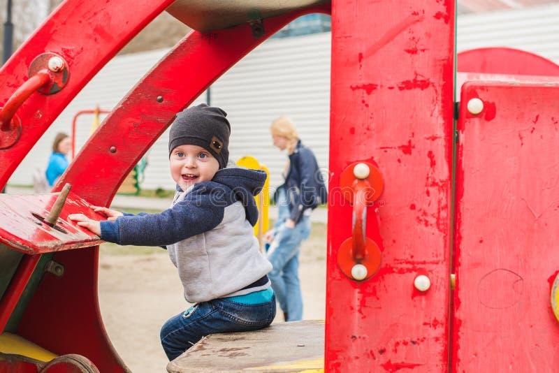 Junge, der ein Spielzeugauto auf dem Spielplatz fährt lizenzfreie stockfotografie