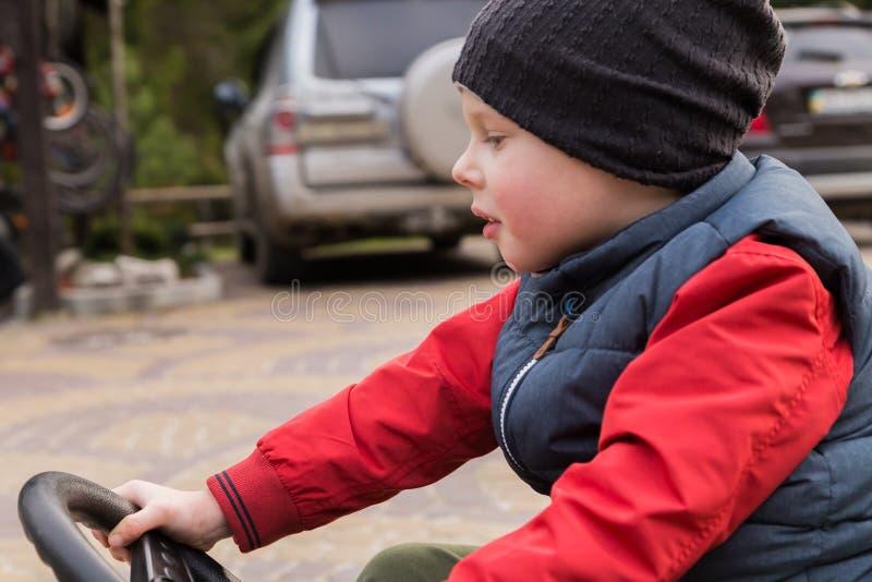 Junge, der ein Spielzeugauto reitet lizenzfreie stockbilder