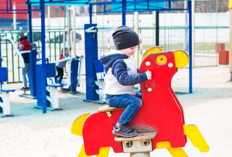Junge, der ein Spielzeugpferd reitet stockbild