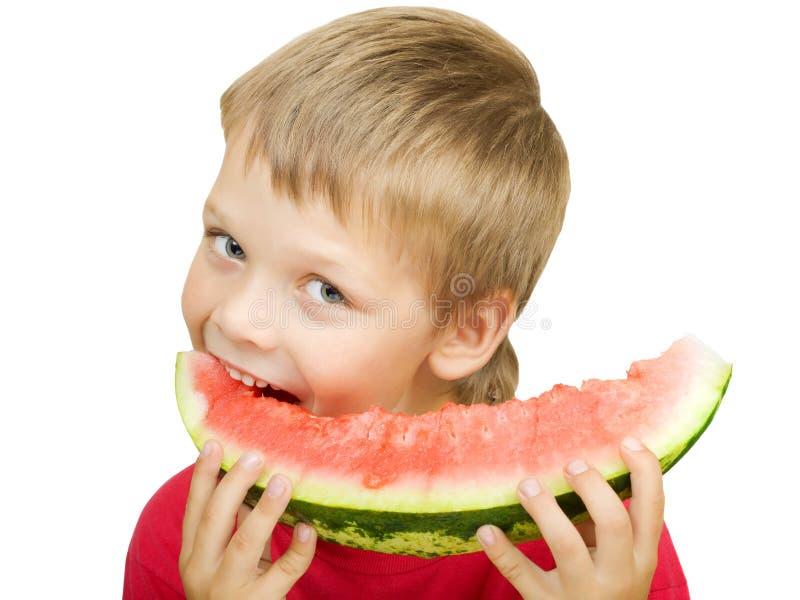 Junge, der ein Stück der Wassermelone isst lizenzfreie stockfotos