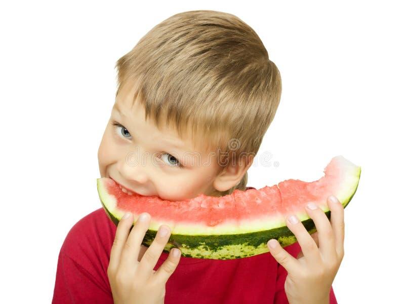 Junge, der ein Stück der Wassermelone isst stockfotografie