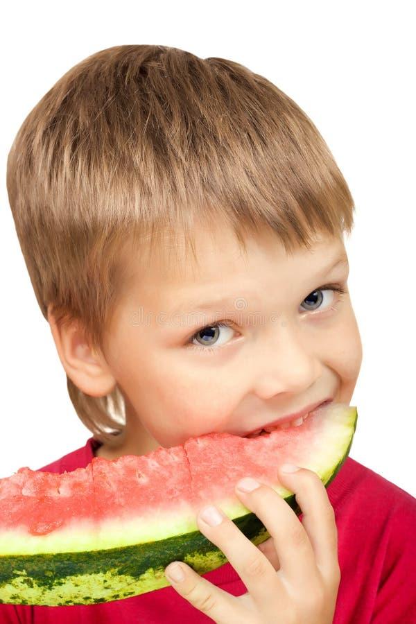 Junge, der ein Stück der Wassermelone isst lizenzfreies stockbild