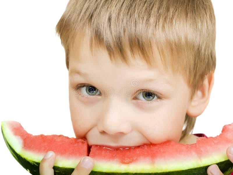 Junge, der ein Stück der Wassermelone isst stockbild