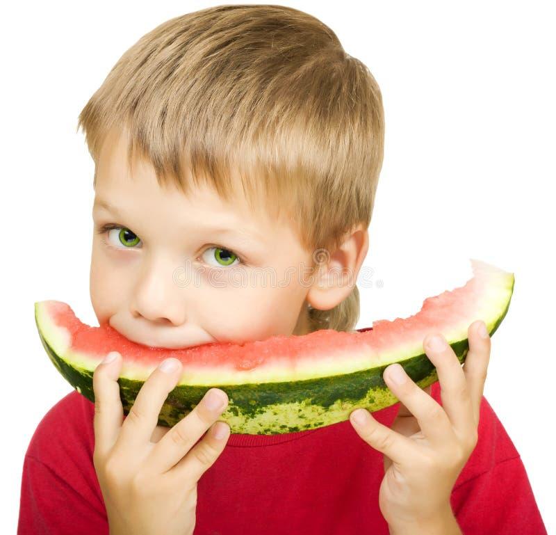 Junge, der ein Stück der Wassermelone isst stockfoto